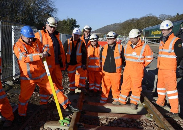 Keith Brown, Cabinet Secretary for Infrastructure. clips the final length of the 30-mile Borders Railway track into place with the installation team.