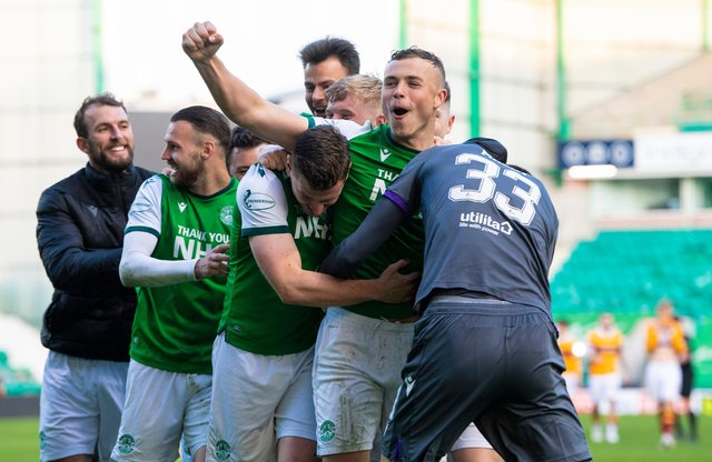 Jubilant Hibs team-mates mob Ryan Porteous after his winning penalty. Picture: SNS