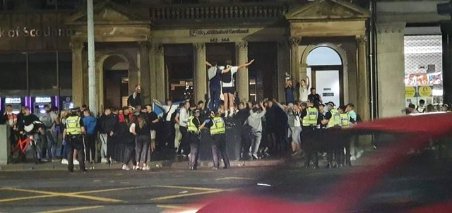 Police seen approaching crowds of football fans celebrating on Prince Street in Edinburgh on Friday night (Photo: William Scally).