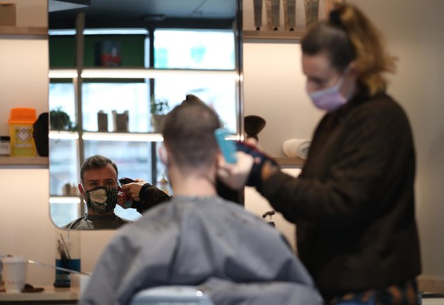 Hairdresser Dana Biezalo with her client Pietro at The Barbery in London. Picture: PA Media