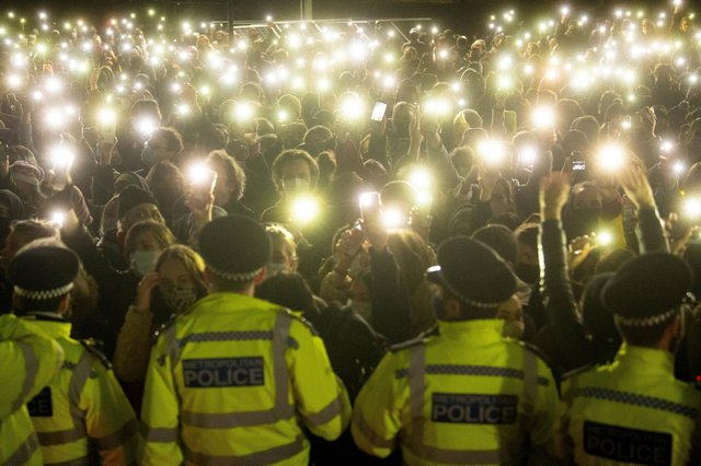 People in the crowd turn on their phone torches at the vigil in Clapham Common that turned ugly