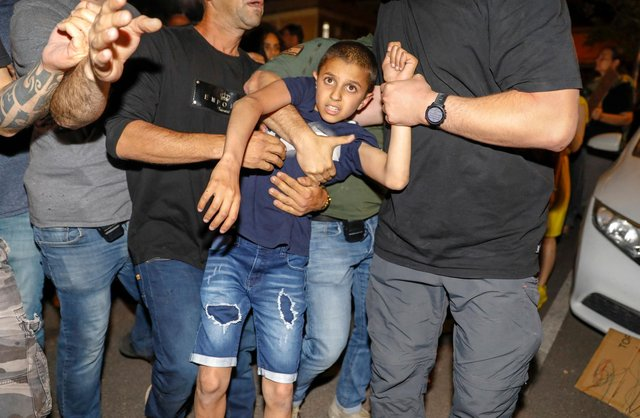 Israeli police detain a boy as Israeli Arabs and left-wing Israelis protest against the purchase of houses in Jaffa, near Tel Aviv by a Jewish religious institution (Picture: Ahmad Gharabli/AFP via Getty Images)