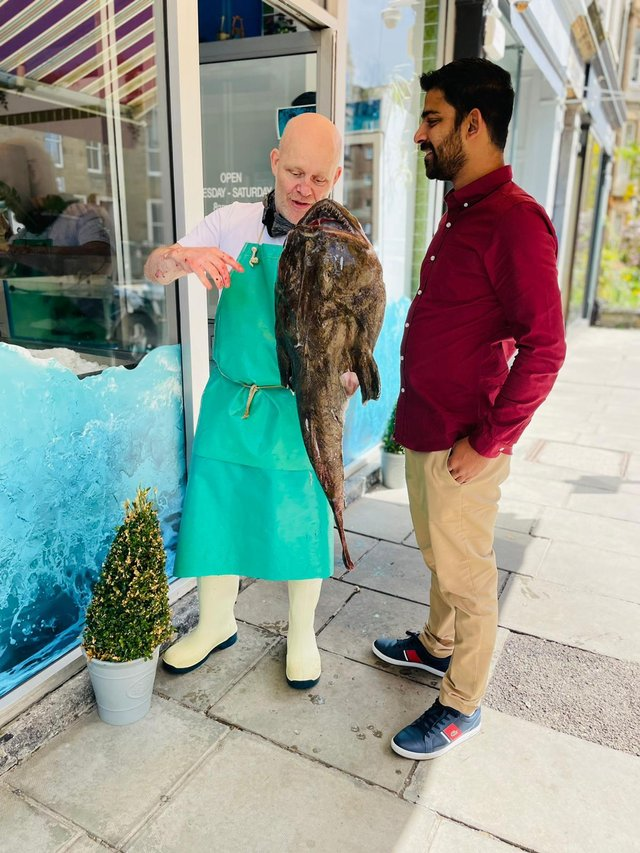 Campbell Mickel of Eddie's Seafood Market with Merwyn and a monkfish