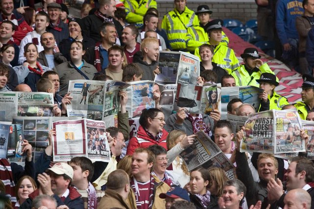 Hearts fans brought newspapers into Ibrox to celebrate their team finishing ahead of Rangers prior to the season's final game. Picture: SNS