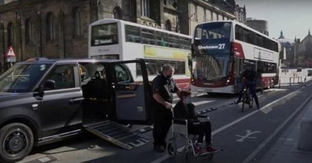 A taxi driver and wheelchair user attempt to negotiate the new road layout