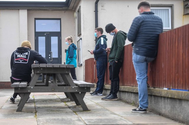 Young people are seen queuing outside a mobile vaccine unit on May 13, 2021 in Lossiemouth, Scotland. (Photo by Peter Summers/Getty Images)