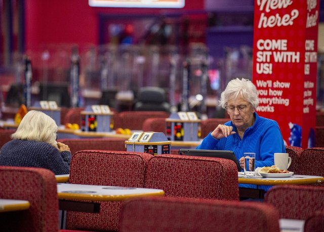 A customer at Buzz Bingo is enjoying a cup of tea and  snack as she plays the game.