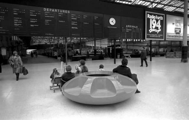Rail passengers sitting on the circular plastic seating on the concourse of Waverley Station, newly modernised in November 1984.