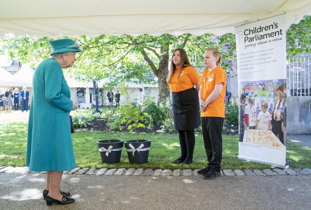 Queen Elizabeth is presented with trees by members of the Children's Parliament during a visit to the Edinburgh Climate Change Institute, as part of her traditional trip to Scotland for Holyrood Week on July 1, 2021 in Edinburgh, Scotland. (Photo by Jane Barlow - WPA Pool/Getty Images)