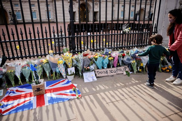 A well-wisher reflects at the floral tributes at the gates of The Palace of Holyroodhouse in Edinburgh (Photo by TOLGA AKMEN/AFP via Getty Images).