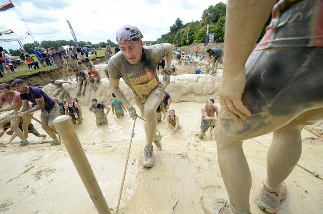 Competitors covered in mud on the 'mud mile' obstacle during a Tough Mudder event on the Badminton Estate, Wiltshire. Picture: PA