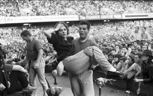 Stewards threw buckets of water to keep fans cool at the U2 concert at Murrayfield stadium Edinburgh, August 1987. This girl was overcome and had to be carried out.
