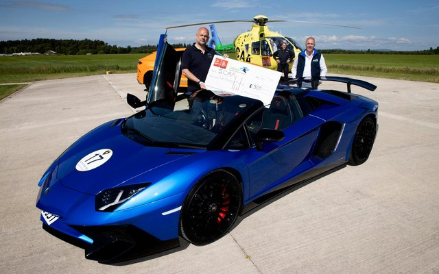 Andy Canning General Manager of Lamborghini Edinburgh pictured handing over a cheque for £500 to Nick Harvey Director of Fundraising & Communictaions at SCAA