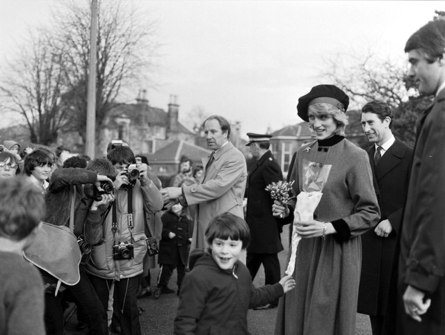Princess Diana and Prince Charles visit Craigroyston in Edinburgh, March 1983. Photographers capture the moment when the Princess of Wales is handed some lucky white heather by nine-year-old Malcolm Smith.