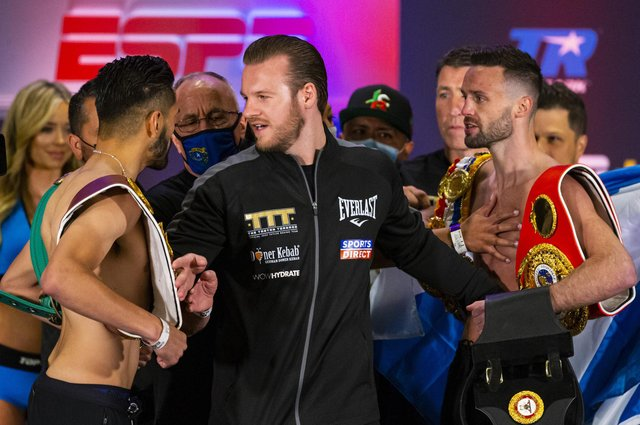 Ben Davison, centre, trainer for Josh Taylor keeps him apart from Jose Ramirez as the two face off following the weigh-in in Las Vegas. Picture: Chase Stevens/AP