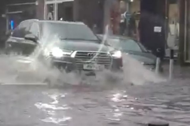 A driver attempts to get through flooded streets in Edinburgh following heavy rain on Sunday (Picture: Jannica Honey)