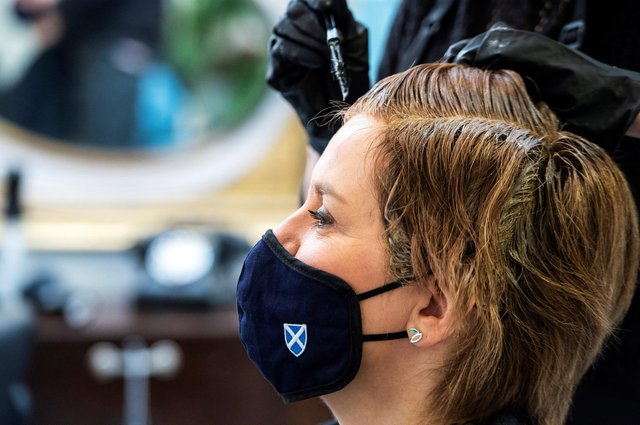 First Minister Nicola Sturgeon, wearing a face covering, has her hair cut by Julie McGuire at Beehive Hair and Make up hairdressers' salon.  (Photo by Fraser Bremner-Pool/Getty Images)