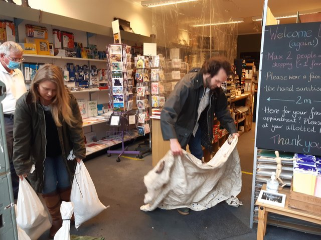 Tom and Lauren Holmes, owners of Henderson Art Shop on Raeburn Place, clean up after the flood