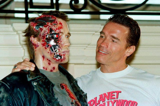 The real Arnold Schwarzenegger poses next to a waxwork of his robotic character in the movie Terminator 2 (Picture: Jacques Demarthon/AFP via Getty Images)