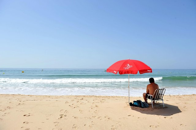 """File photo dated 12/06/14 of a man sitting under a parasol on the beach at Praia da Luz, Portugal. Moving Portugal off the UK's green list is """"an overreaction"""", an epidemiologist in the popular holiday destination has claimed. Issue date: Friday June 4, 2021. PA Photo. Professor Henrique Barros, president of Portugal's National Health Council, said the country's overall coronavirus situation is """"relatively stable"""". He made the comments after Communities Secretary Robert Jenrick said positive cases had doubled in the last three weeks in Portugal. See PA story HEALTH Coronavirus. Photo credit should read: Nick Ansell/PA Wire"""