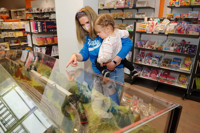 Anna Riley and her daughter, Phoebe, watch an interaative Hornby Flying Scotsman model in the toys section.