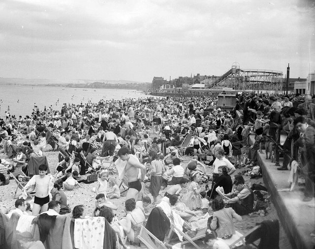Crowds of holiday-makers cram onto Portobello Beach in May 1952 with the rollercoaster and funfair in the background.