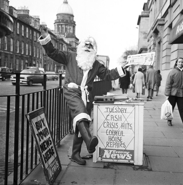 An Evening News vendor gets into the Christmas spirit by dressing as Santa Claus at his pitch outside Frasers department store in Princes Street Edinburgh, December 1986.