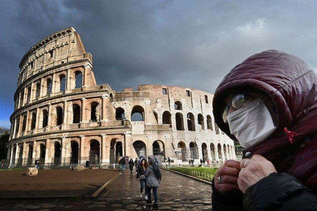 A man wearing a protective mask passes by the Coliseum in Rome (Photo: Alberto PIZZOLI / AFP) (Photo by ALBERTO PIZZOLI/AFP via Getty Images)