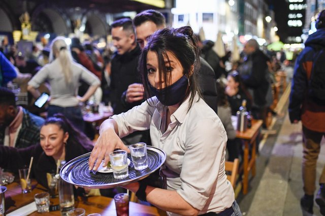 A waitress serves drinks at tables outside a pub in Soho, London, on the day some of England's coronavirus lockdown restrictions were eased (Picture: Alberto Pezzali/AP)