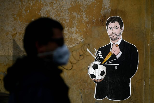 Grafitti entitled 'Il Golpe Fallito', the 'failed coup', by Italian artist Laika, showing Juventus president Andrea Agnelli, an architect of the European Super League plan, puncturing a football, near the headquarters of the Italian Football Federation in Rome (Picture: Filippo Monteforte/AFP via Getty Images)