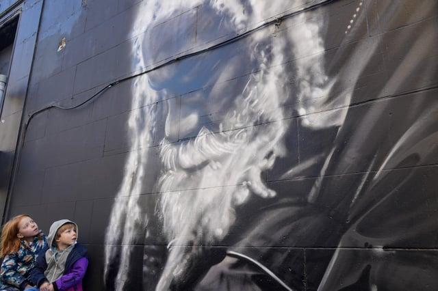 Bonnie Thompson, age 6 and Euan Thompson, age 5 visit the mural of Arthur Williams on Arthur Street, Leith