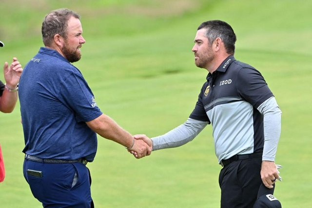 Defending champion Shane Lowry shakes hands with Louis Oosthuizen after their opening round in the 149th Open at Royal St George's. Picture: Paul Ellis/AFP via Getty Images.