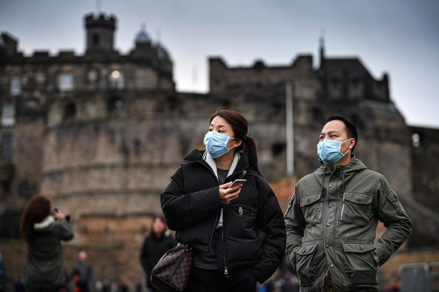Tourists wearing face masks visit Edinburgh Castle in January last year (Picture: Jeff J Mitchell/Getty Images)
