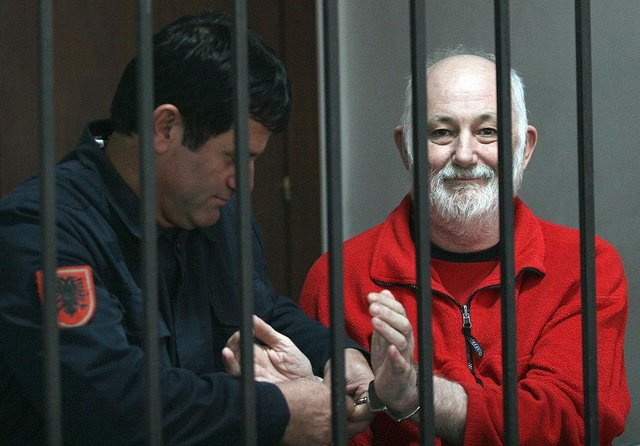 A Police officer remove the handcuffs from Britton David Brown, 57, before the verdict in court, where he was sentenced him to 20 years in jail for sexually abusing minors, in Tirana on November 19, 2008. Picture: GENT SHKULLAKU/AFP via Getty Images