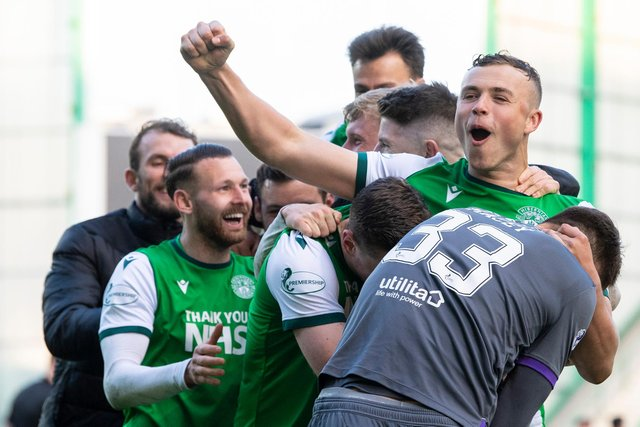 Hibs defender Ryan Porteous is mobbed by his team-mates after scoring the winning penalty.