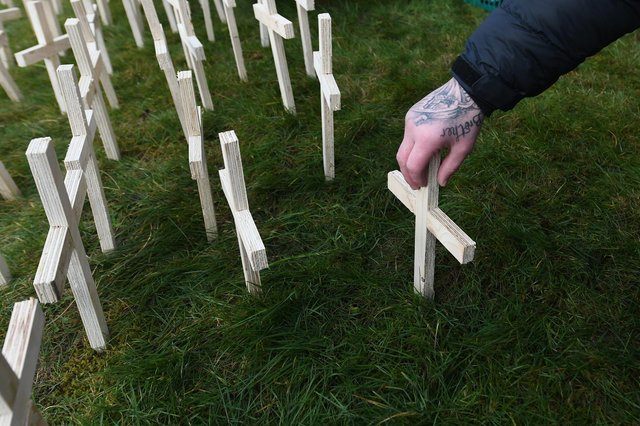 A man leaves a cross for his brother at a memorial for drug-death victims (Picture: John Devlin)