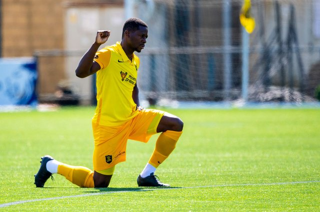 Livingston midfielder Marvin Bartley supports football's anti-racism movement by taking a knee ahead of a match this season. Photo by Ross MacDonald / SNS Group