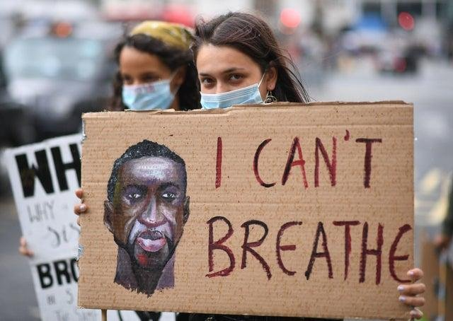 People hold banners during a Black Lives Matter protest rally as it passes near to Victoria station, London, in memory of George Floyd who was killed on May 25 while in police custody in the US city of Minneapolis.