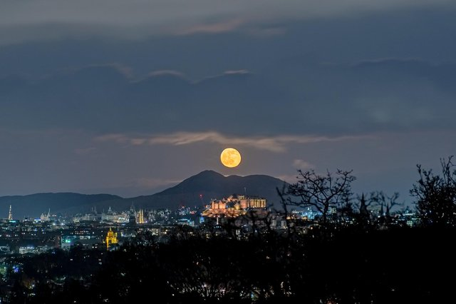 This spectacular image shows a ghostly, spectre-like  moon hanging above Edinburgh Castle