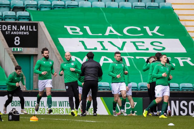 The Hibs players warm up in front of a Black Lives Matter banner at Easter Road