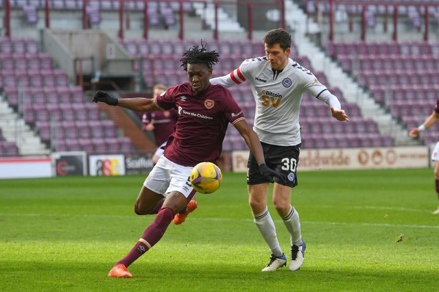 Hearts striker Armand Gnanduillet and Ayr United's Jack Baird in action at Tynecastle.