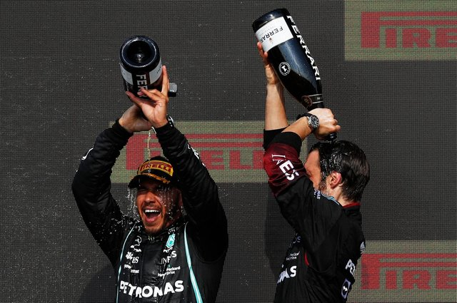 Lewis Hamilton, left, pours champagne on his head on the podium after winning the Formula 1 Grand Prix at Silverstone (Photo: Adrian Dennis / AFP via Getty Images)