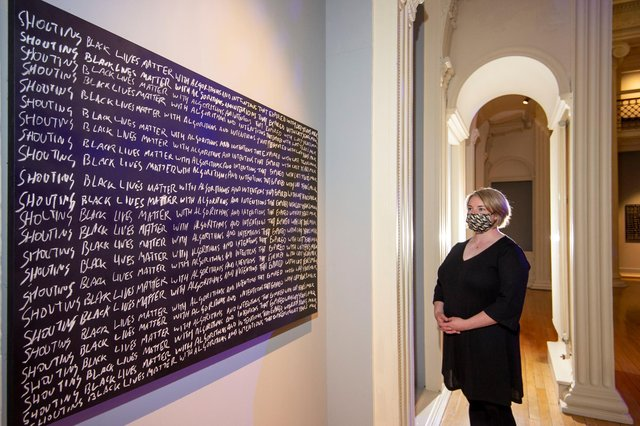 Exhibitions manager Melissa MacRobert with Larry Achiampong's work, Detention. Picture: Neil Hanna