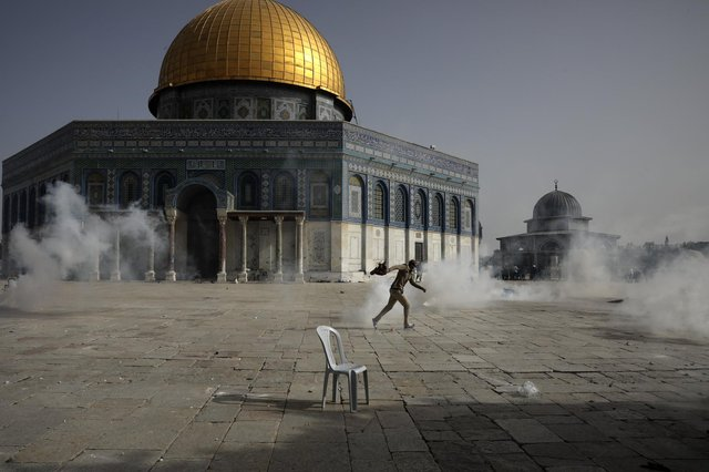 A Palestinian man runs away from tear gas during clashes with Israeli security forces in front of the Dome of the Rock Mosque in Jerusalem (Picture: Mahmoud Illean/AP)