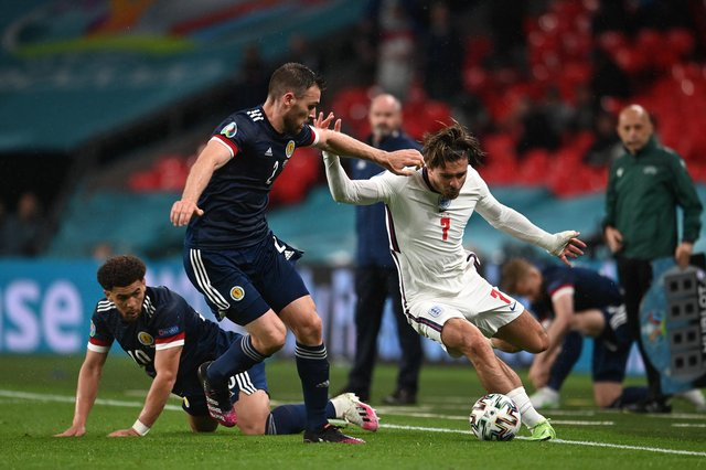 LONDON, ENGLAND - JUNE 18: Jack Grealish of England runs with the ball whilst under pressure from Stephen O'Donnell and Che Adams of Scotland during the UEFA Euro 2020 Championship Group D match between England and Scotland at Wembley Stadium on June 18, 2021 in London, England. (Photo by Andy Rain - Pool/Getty Images)