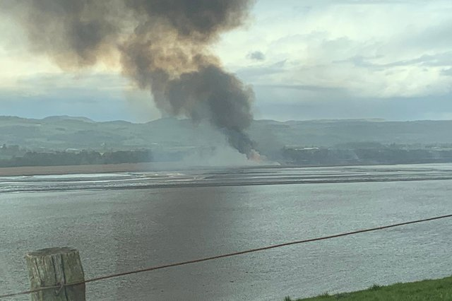 Thick black smoke billows up from the reed beds near Errol Airfield, Perthshire.