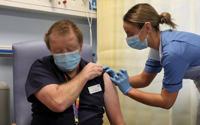 Deputy charge nurse Katie McIntosh giving Clinical Lead of Outpatient Theatres Andrew Mencnarowski, a Covid vaccine at the Western General Hospital in Edinburgh, on December 8.