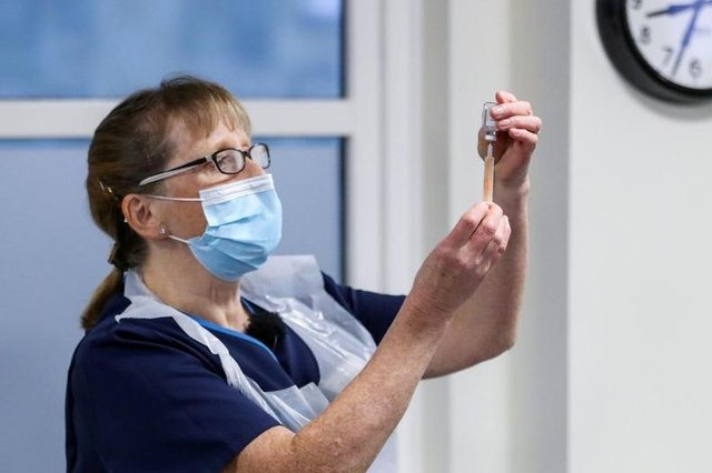 Practice Nurse Ruth Davies holds a vial of the Oxford/AstraZeneca coronavirus vaccine at Pentlands Medical Centre in Edinburgh.