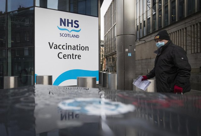 A member of the public outside the main entrance to the coronavirus mass vaccine centre at the Edinburgh International Conference Centre. Picture date: Monday February 1, 2021.
