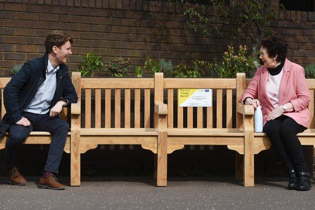 Sovereign Assist co-founder Andrew Fyfe and Helen Feeley, 73, chat on a specially designed 3m bench dubbed the 'Chatty Bench'  outside Orchard Brae House, Edinburgh.